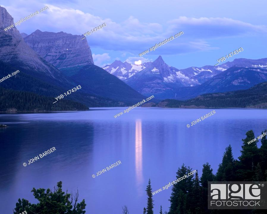 Stock Photo: Full moon sets at dawn over Fusillade Mountain and St  Mary Lake, Glacier National Park, Montana, USA.