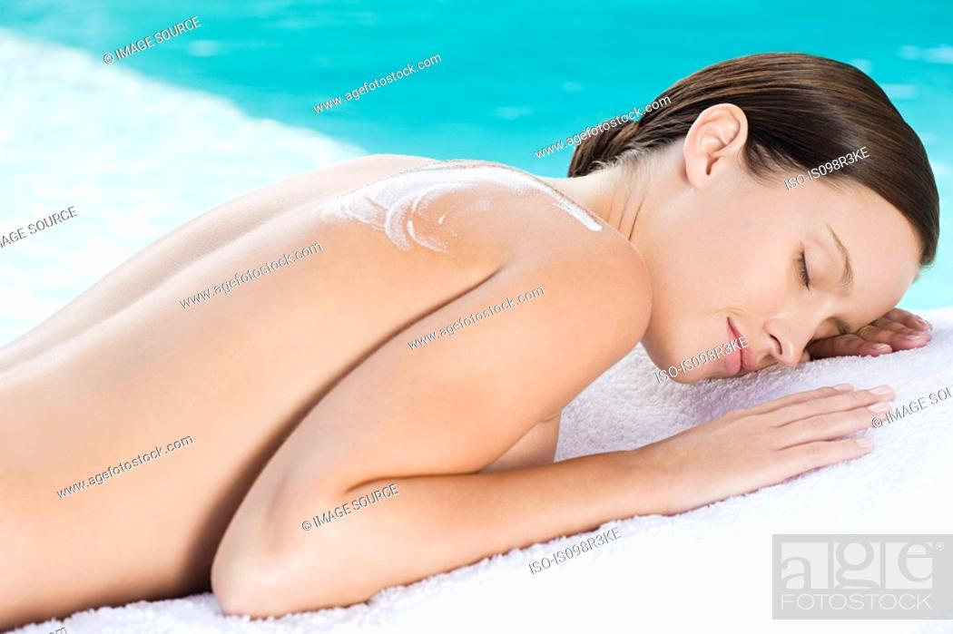 Stock Photo: Young woman lying on towel by the pool with lotion on shoulder.