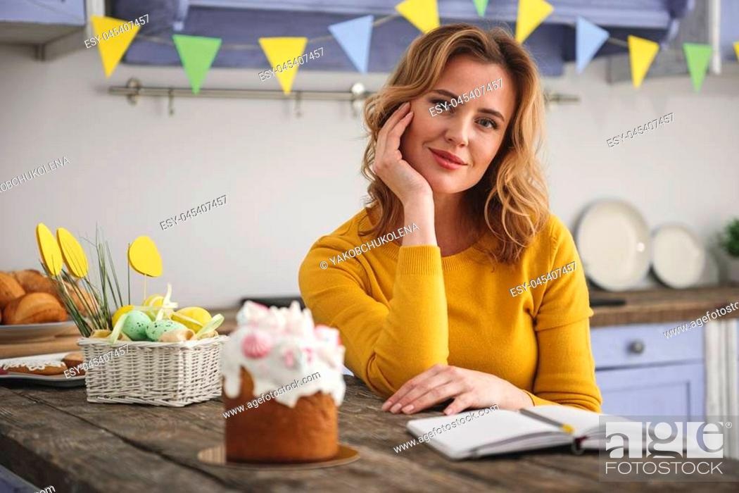 Stock Photo: Portrait of glad pretty woman sitting in country style kitchen, she is looking at camera and smiling. Beautiful cake and easter eggs are on table.