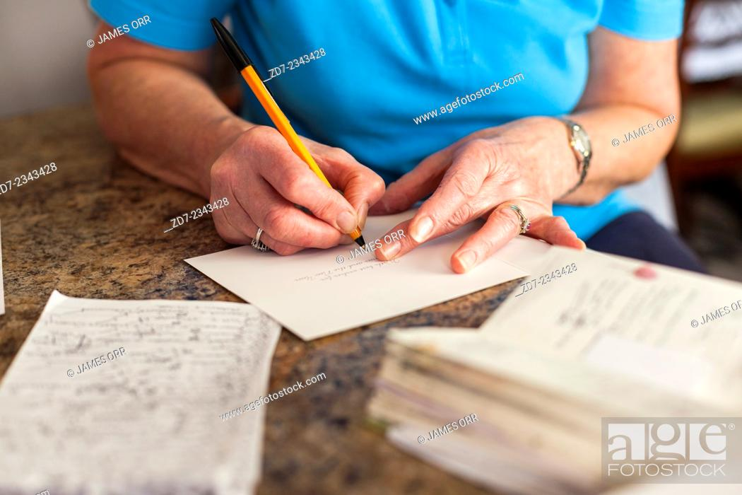 Stock Photo: Middle aged woman writing Christmas cards.