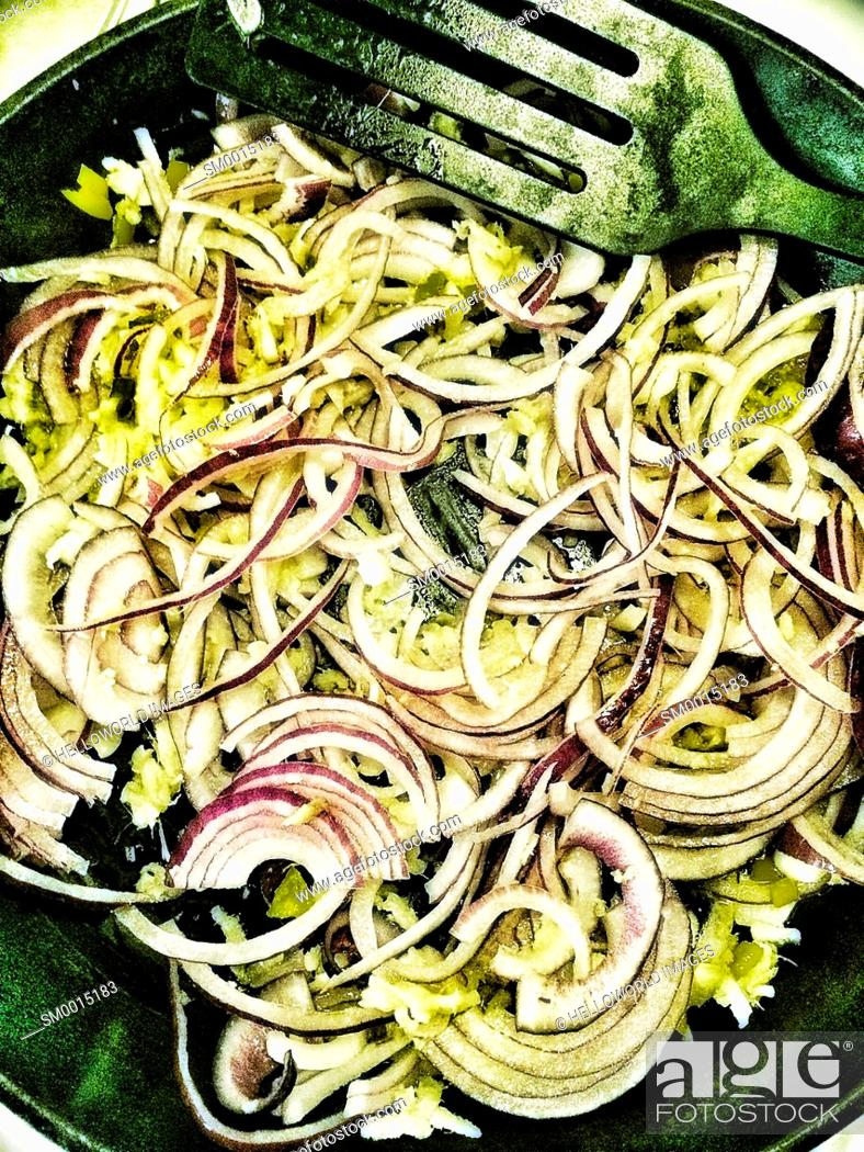 Stock Photo: Red onions frying sautéing in frying pan.