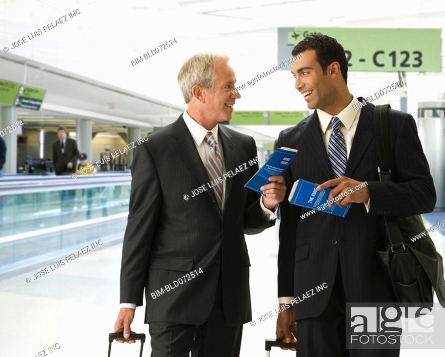 Stock Photo: Businessmen holding tickets in airport.