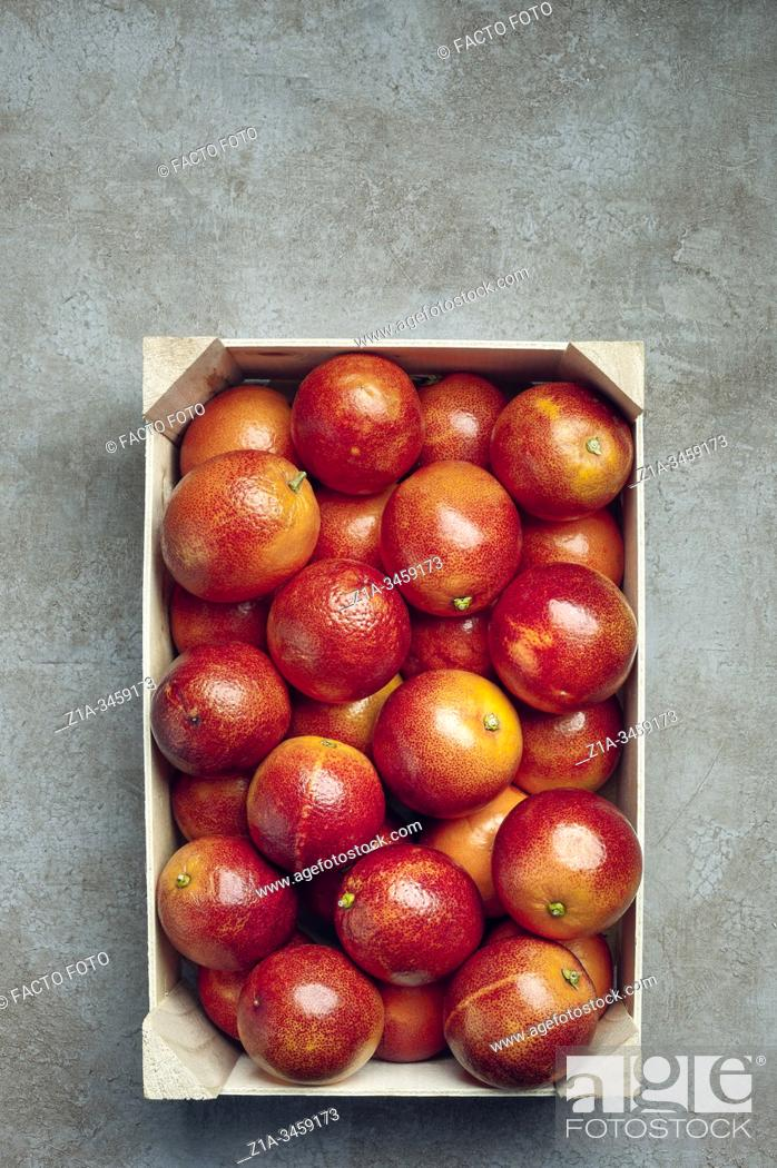 Imagen: Blood oranges in a wooden box on a grey textured background.