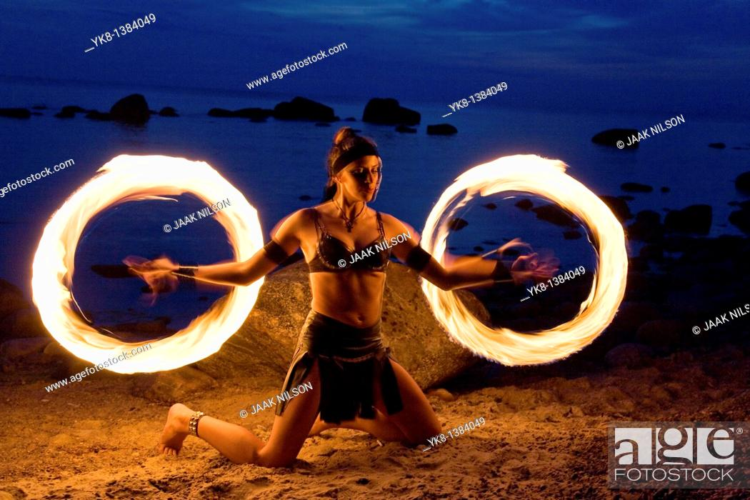 Stock Photo: Semi Nude Woman Fire Dancer in Costume Juggling Torches by Water.