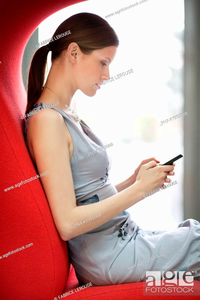 Stock Photo: Businesswoman text messaging on a mobile phone in an office.