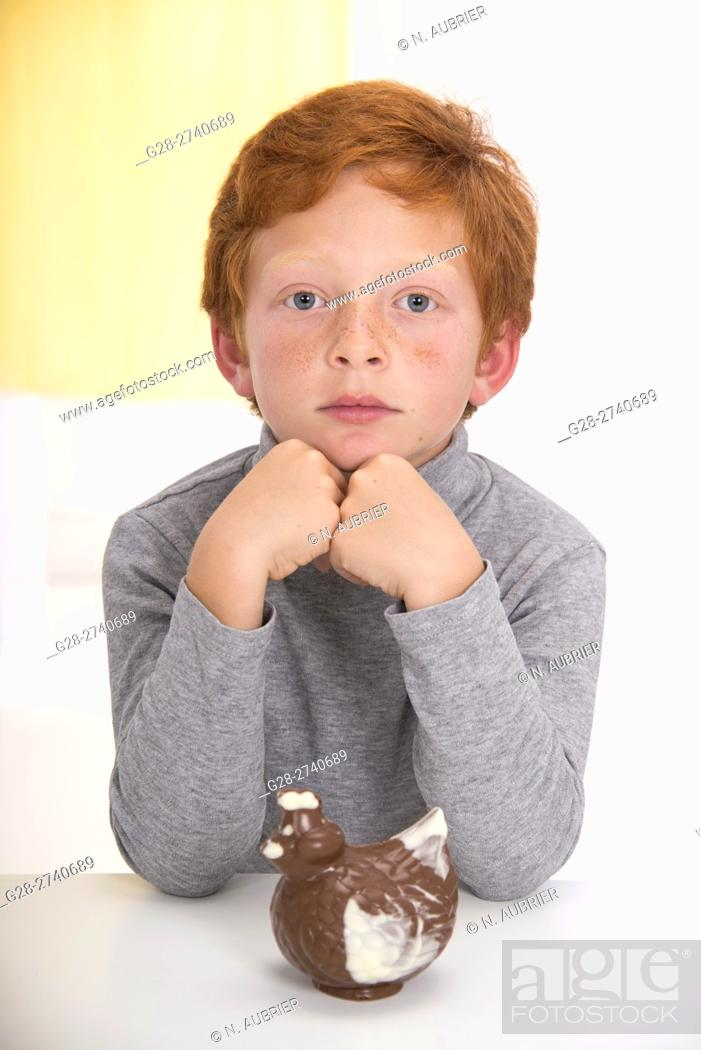 Stock Photo: Little boy with red hair, elbows on the table, head resting on his hands, thoughtful in front of an easter chocolate hen.