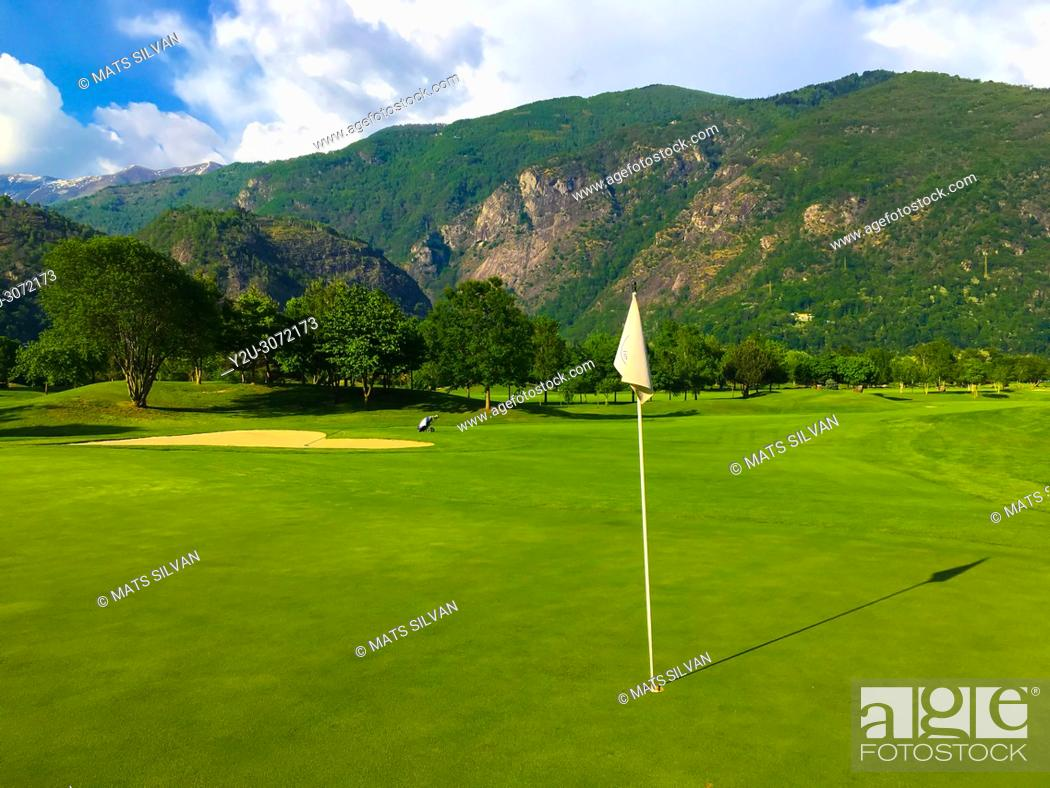 Stock Photo: Golf Course Gerre Losone with Golf Green with Flag and Mountain in Losone, Ticino, Switzerland.