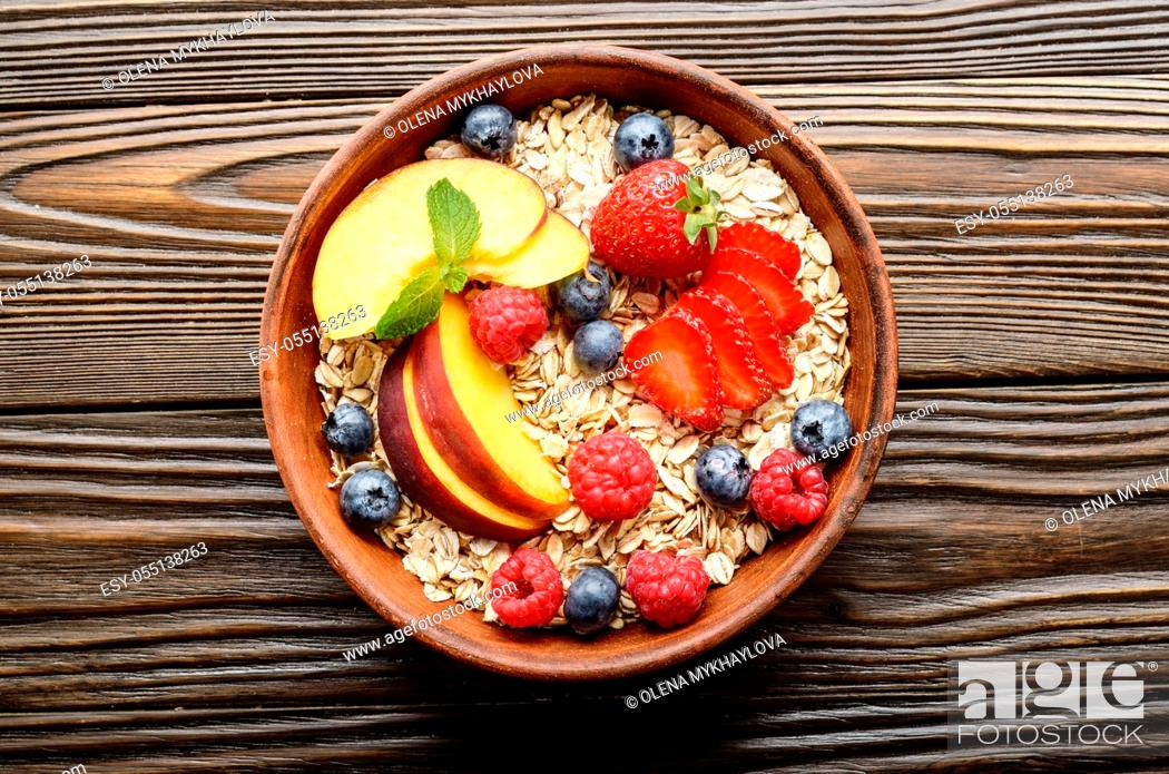 Stock Photo: Flat lay of fruit healthy muesli with peaches strawberry almonds and blackberry in clay dish on wooden kitchen table.