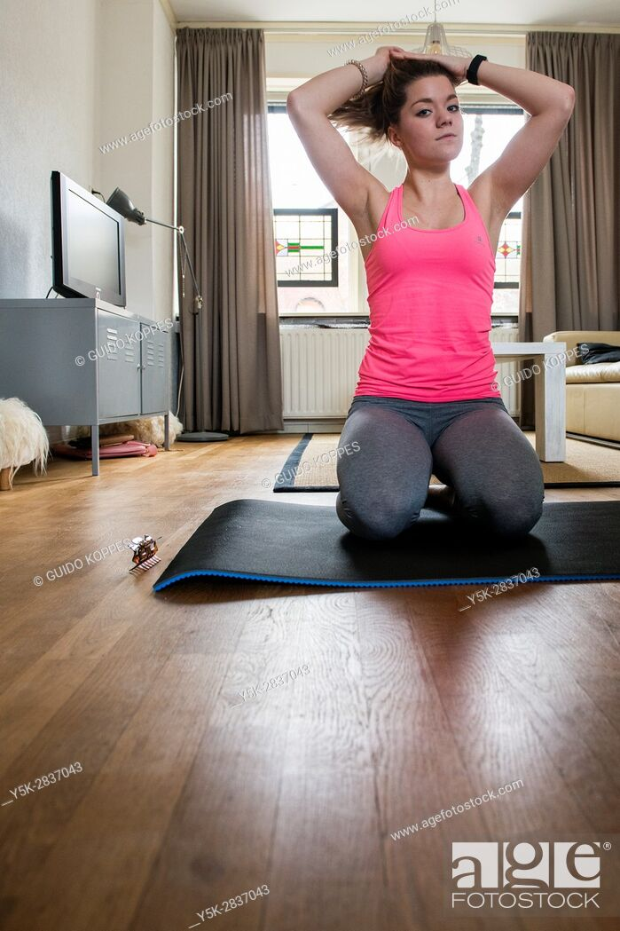 Stock Photo: Tilburg, Netherlands. Young adult girly woman working out inside her living room.