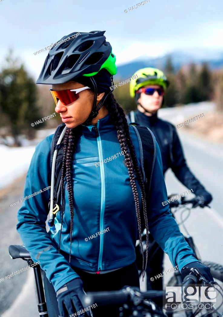 Stock Photo: Two mountain bikers standing on road outdoors in winter, resting.