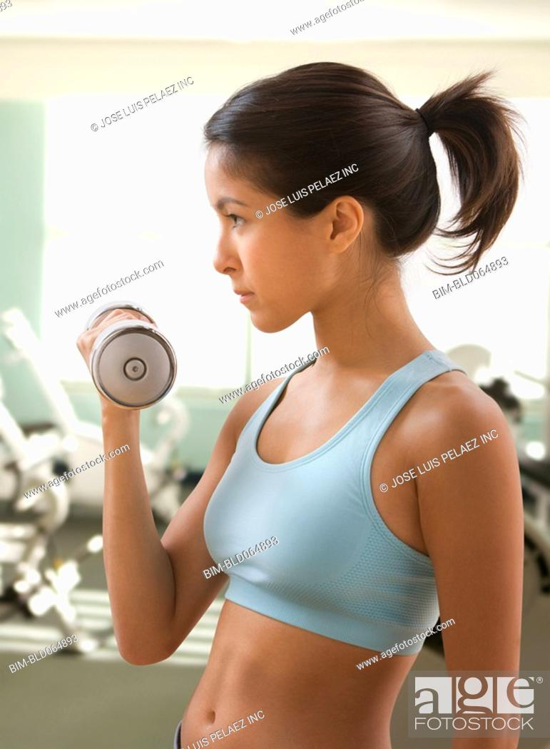 Stock Photo: Eurasian woman lifting dumbbells in health club.