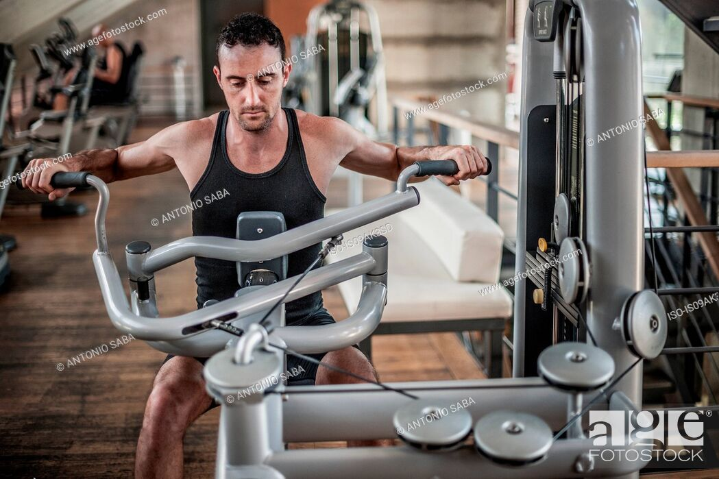 Stock Photo: Mid adult man using weight equipment.