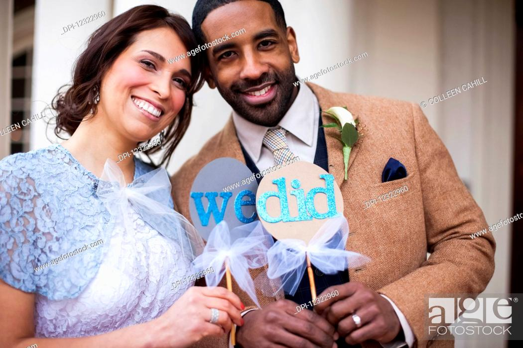 Stock Photo: A bride and groom pose with signs symbolizing their wedding vows; Portland, Oregon, United States of America.