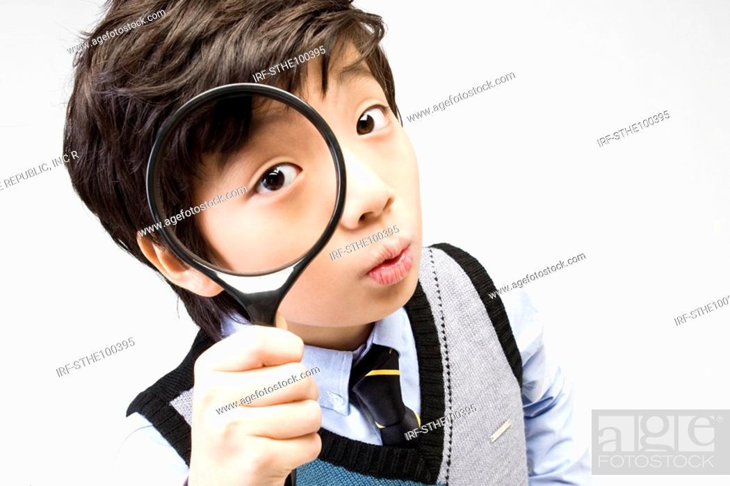 Photo de stock: boy holding a magnifier.