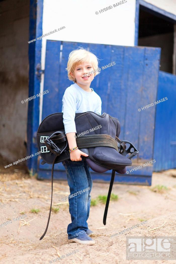 Stock Photo: Boy carrying horse saddle.
