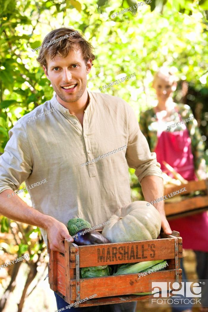 Stock Photo: Smiling man holding a crate of vegetables.