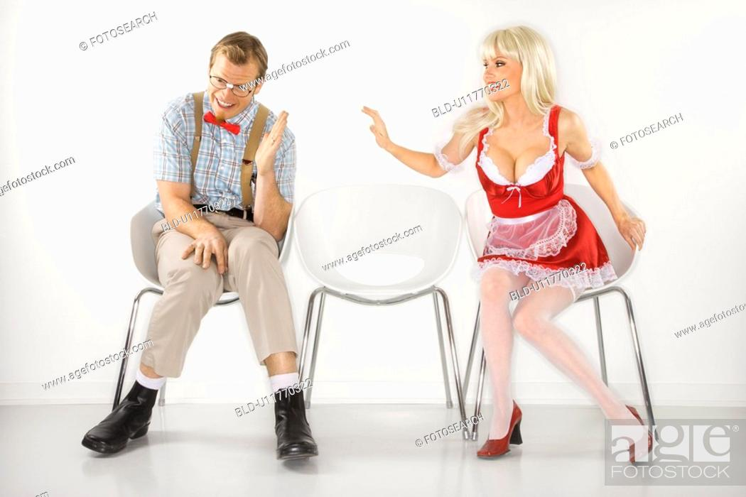 Stock Photo: Woman sitting reaching over to shy young man dressed like nerd.