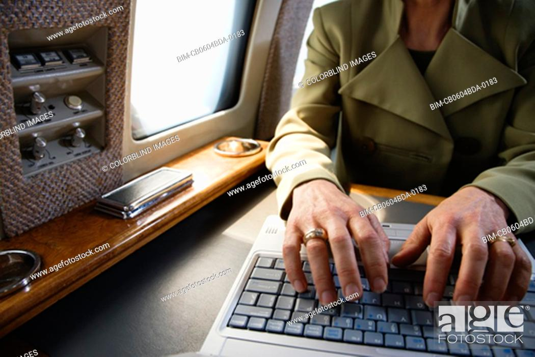 Stock Photo: Close up of businesswoman using laptop on private airplane.