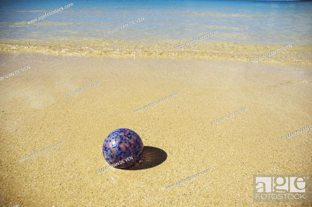 Stock Photo: Art glass float on sandy beach with calm ocean.