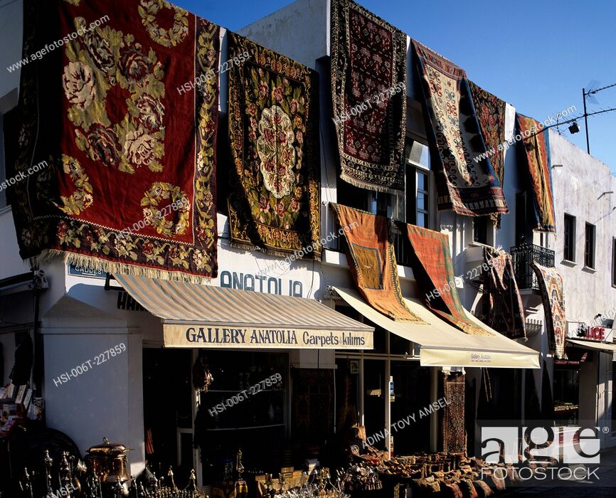Stock Photo: Morocco. Marrakech. Carpets displayed on walls outside shop.