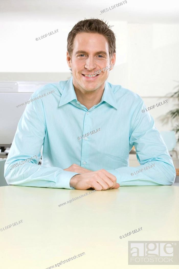 Stock Photo: Germany, Munich, young man in office, arms crossed, smiling, portrait, close-up.