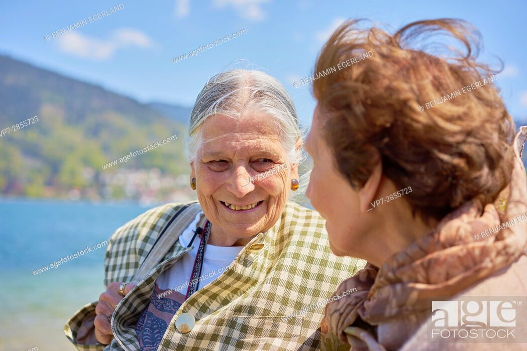 Photo de stock: Happy senior woman enjoying togetherness with old friend at lake Tegernsee in Bavaria, Germany.
