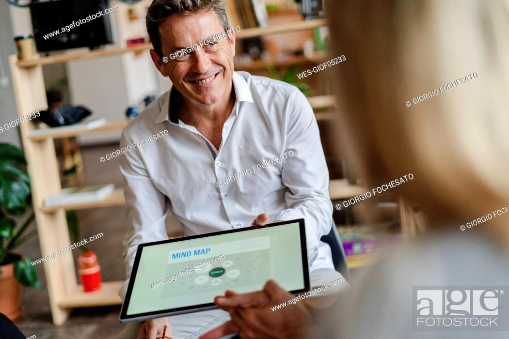 Stock Photo: Smiling businessman holding tablet with a mind map during a presentation in loft office.