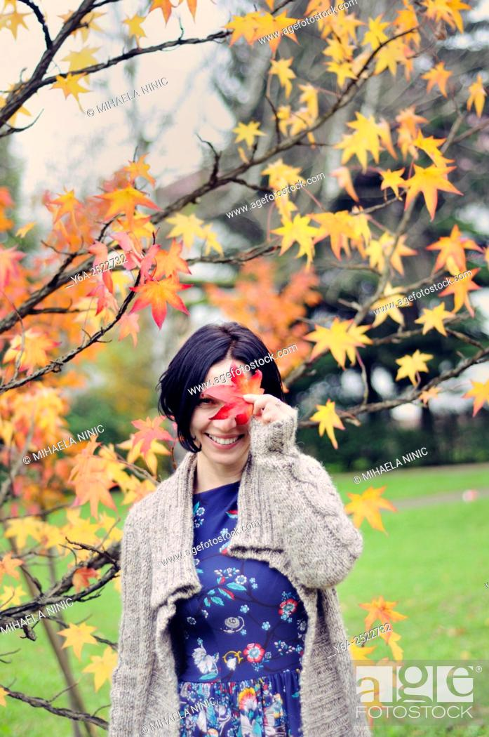 Imagen: Smiling mid adult woman holding leaf close to her face, autumn.