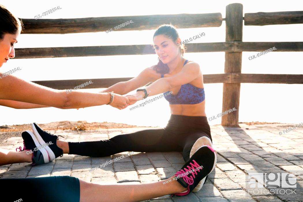 Stock Photo: Two young women training together on sea waterfront.