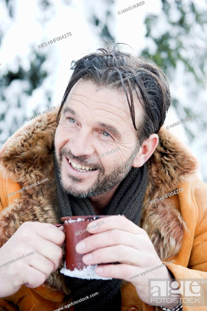 Stock Photo: Austria, Salzburg County, Mature man drinking tea, smiling.
