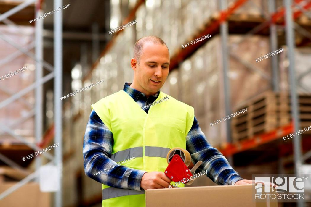 Stock Photo: logistic, delivery, shipment, people and export concept - happy man in safety vest packing box or parcel with scotch tape at warehouse or mail storage.