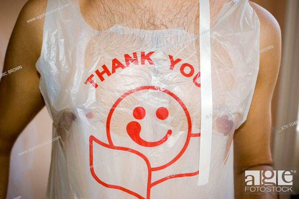 Stock Photo: A man wears a plastic shopping bag as a shirt.