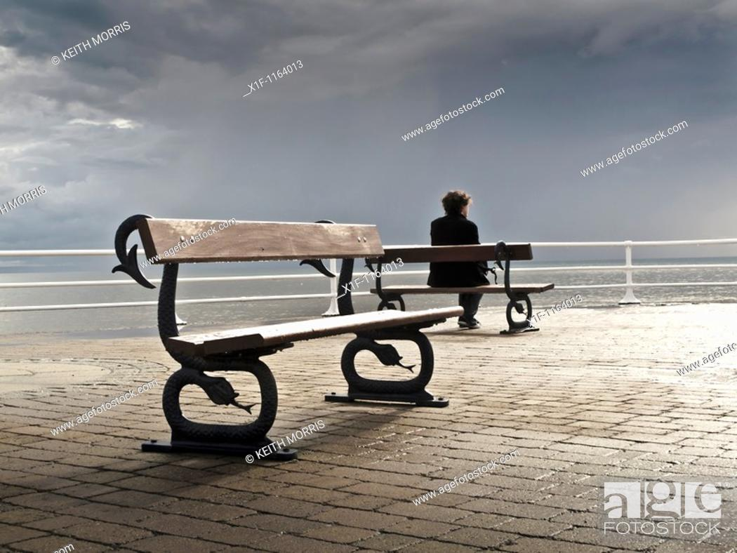 Stock Photo: A man sitting alone on a bench on the promenade, grey overcast July summer afternoon, Aberystwyth Wales UK.