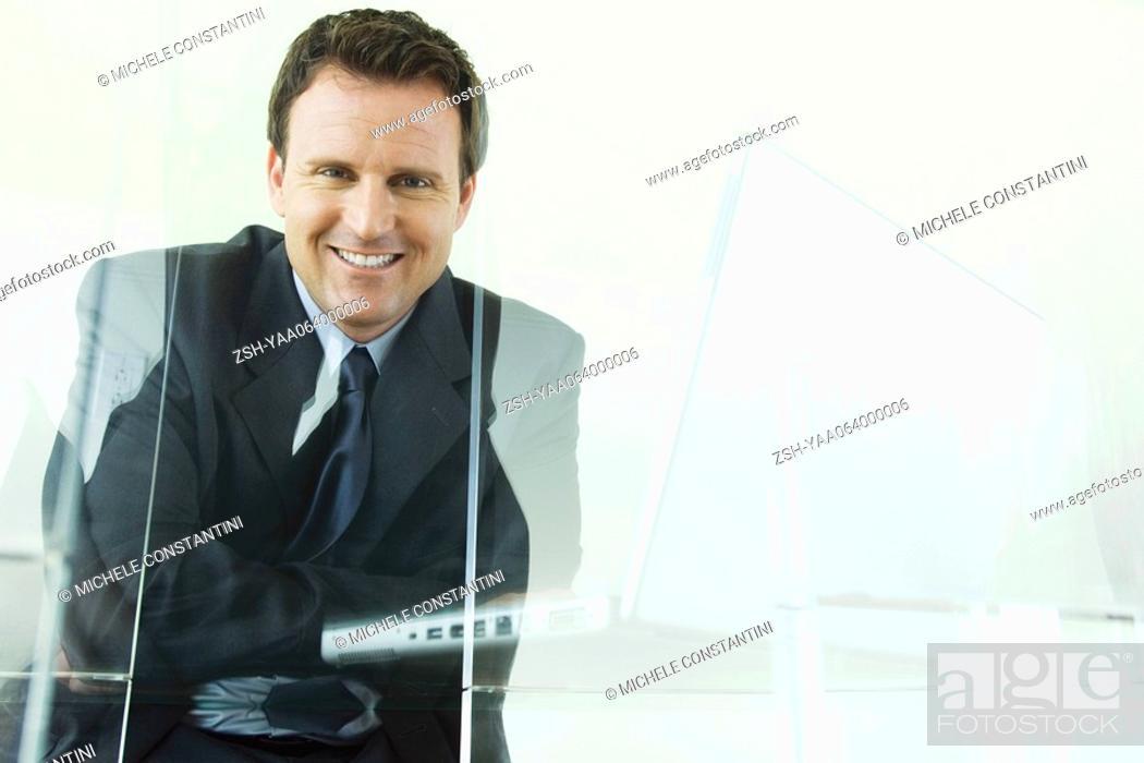 Stock Photo: Businessman sitting next to laptop computer, smiling at camera.