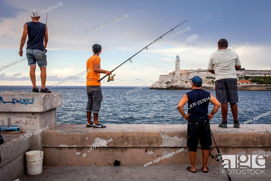 Stock Photo: Fishermen, in Malecón, on the background the Castillo de los Tres Reyes del Morro, La Habana, Cuba.