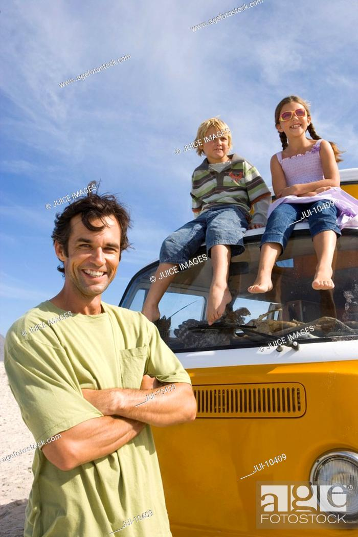 Stock Photo: Man on beach with arms crossed by son and daughter 5-9 on roof of camper van, portrait, low angle view.