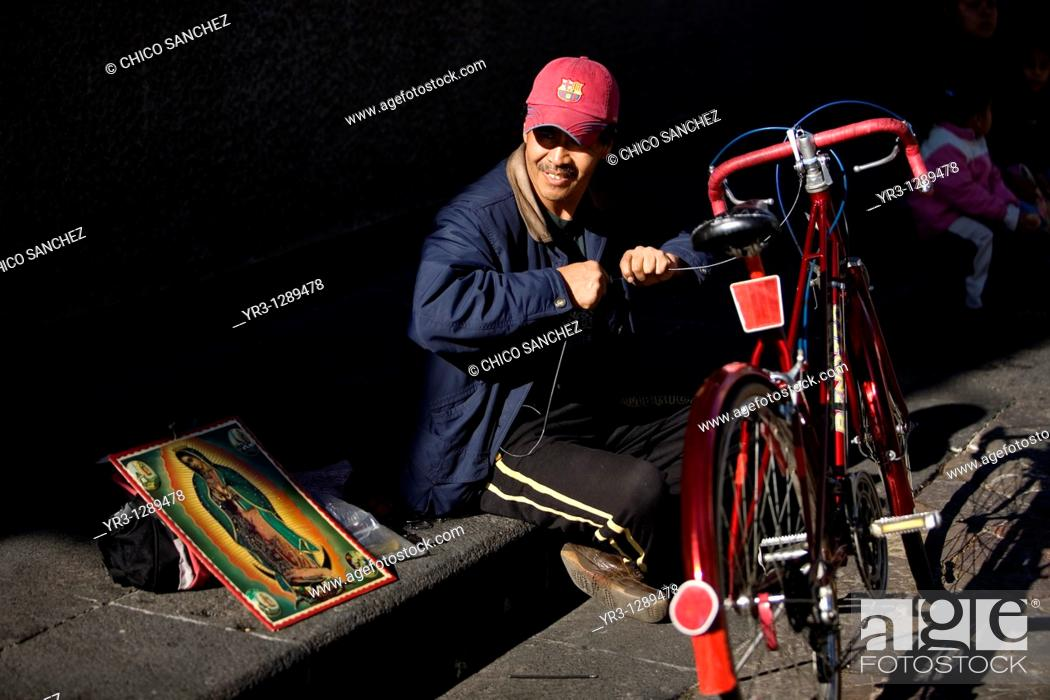 Stock Photo: A man repairs his bicycle outside the Our Lady of Guadalupe Basilica in Mexico City, December 9, 2010  Hundreds of thousands of Mexican pilgrims converged on.