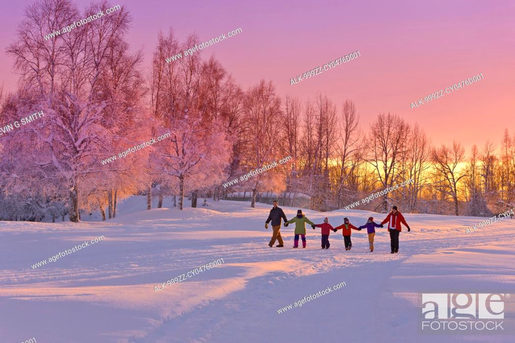 Stock Photo: Family group, holding hands, walk on a snow path at sunset with a birch forest in the background, Russian Jack Springs Park, Anchorage, Southcentral Alaska.