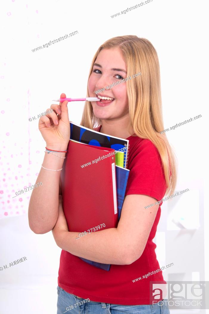 Stock Photo: young school girl, 15 year old, in red, with a broad smile, holding her copybooks in her arms, with her pen in her mouth.