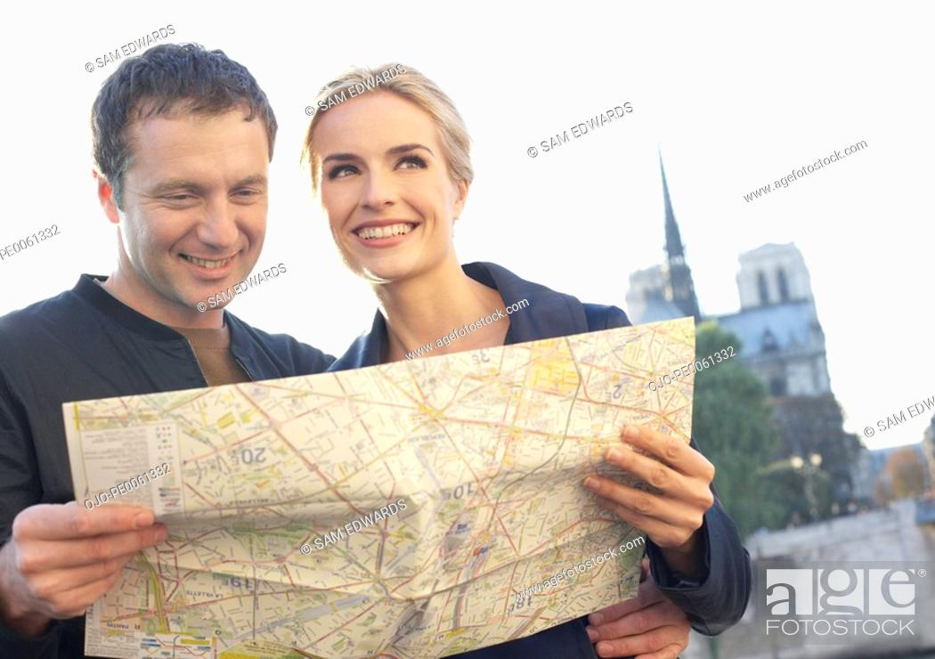 Stock Photo: Couple outdoors with map smiling.