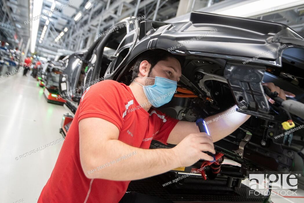 Stock Photo: 12 May 2020, Baden-Wuerttemberg, Stuttgart: An employee of Porsche AG wears a mouthguard in the production of the battery electric driven sports car Porsche.