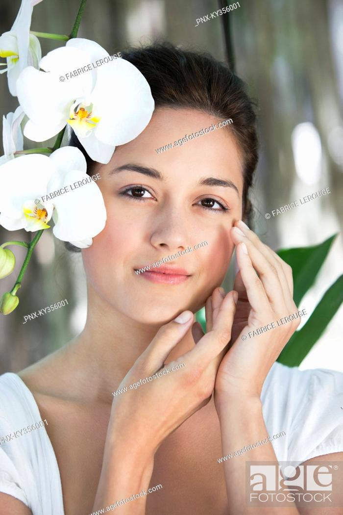 Stock Photo: Portrait of a beautiful young woman with flowers.