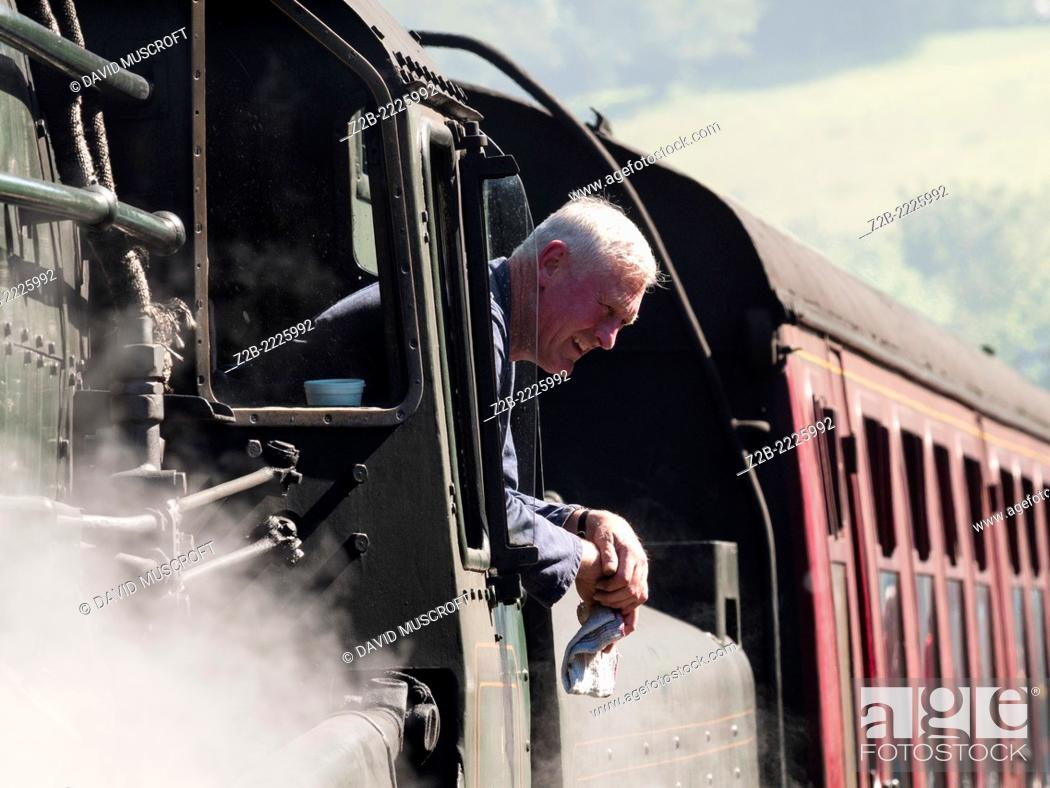 Stock Photo: Train driver of a vintage steam locomotive at Grosmont station on the North Yorkshire Moors Railway ,near Whitby, North Yorkshire, UK.