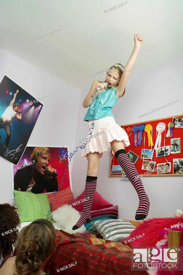 Stock Photo: Girl jumping on bed singing friends watching from floor.