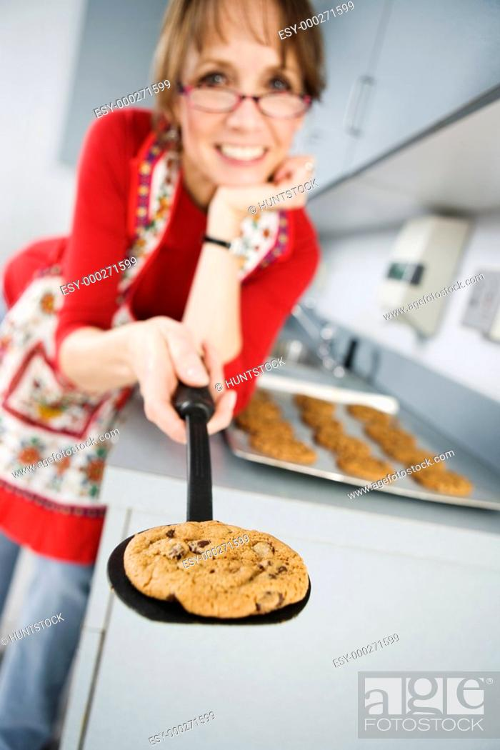 Stock Photo: Portrait of a woman holding baked cookie on food turner.