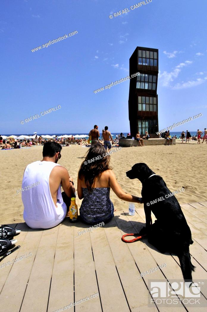 Stock Photo: Couple with a black dog. Sculpture 'The wounded star' L'estel ferit by Rebecca Horn at Barceloneta beach, 1992. Barcelona, Catalonia, Spain.