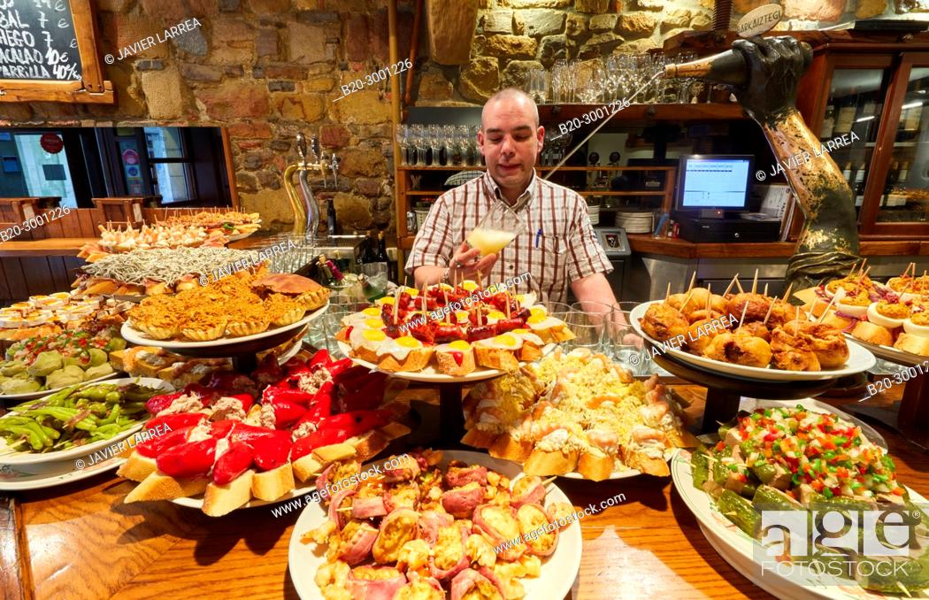 Stock Photo: Waiter serving cider, Pintxos, Bar Taberna Aralar, Parte Vieja, Old Town, Donostia, San Sebastian, Gipuzkoa, Basque Country, Spain.