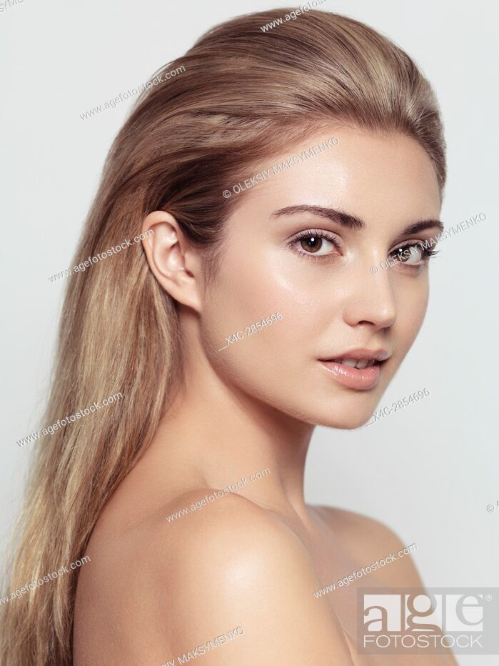 Stock Photo: Beauty portrait of young exotic woman face with light brown hair and natural clean look isolated on light gray background.