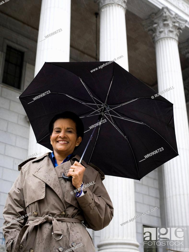 Stock Photo: Low angle view of a woman holding an umbrella and smiling.
