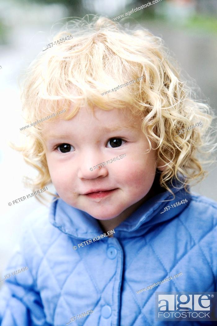 Stock Photo: Porrtait of a young girl in a blue jacket with curly blond hair.